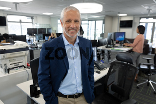 Portrait of senior businessman smiling at modern office