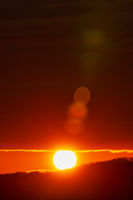Rising of the sun in mountains, red sun disk rises from tops of mountain range. Beautiful natural lens flare in orange sky