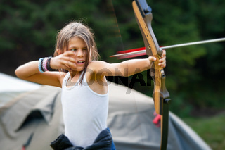 Gipsy girl enjoying with the arrow leaving the bow in a glade camp