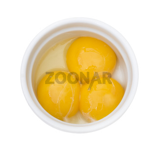 Bright yellow egg yolks in a white bowl on white background