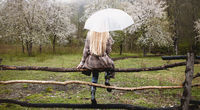 Solitary woman enjoying nature in blooming orchard in raining cool weather