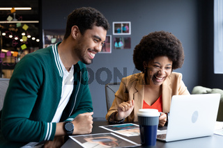 Happy diverse businessman and businesswoman using laptop in creative office