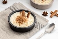 Creamy rice pudding with cinnamon in bowl on white marble table
