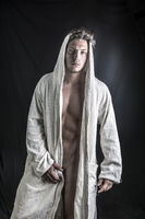 Handsome young man wearing white bathrobe in studio shot