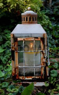 alte rostige Laterne mit brennender Kerze