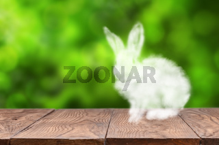 Cloud Easter Bunny on a wooden table against blurred green background.