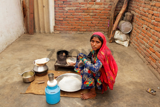 Indian woman prepare food in a small courtyard of her house.