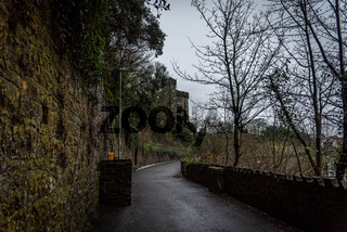 KILKENNY, IRELAND, DECEMBER 23, 2018: Pathway between Kilkenny Castle and River Nore, with wonderful medieval aspect, wet moldy exterior walls and covered with vegetation growing as the time goes by.