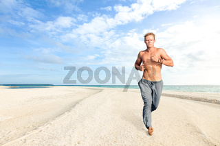 Man running on sand of tropical beach