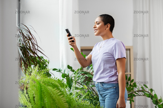 african american woman with smartphone at home