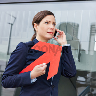 Geschäftsfrau mit Pfeil beim Telefonieren mit Smartphone