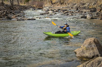 senior paddler in  inflatable whitewater kayak