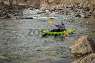 senior paddler in  inflatable whitewater kayak