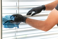 professional cleaner cleaning window blinds in an apartment with a blue micro fiber cloth
