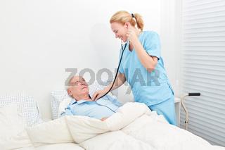 Krankenschwester mit Stethoskop hört Patient ab