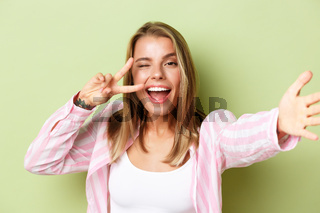 Close-up of stylish blond girl with tattoo, wearing pink shirt, taking selfie, showing peace sign at camera and smiling, standing over green background