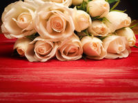 Bouquet of white roses on a red wooden table