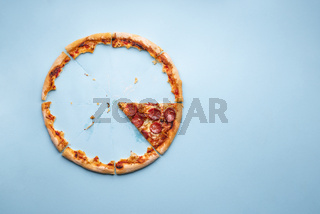 Last piece of pizza pepperoni on blue background