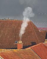 Dächer eines alten Dorfes mit einem rauchenden Kamin und Textfreiraum