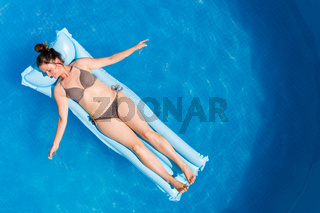Young woman in bikini on Air Mat Mattress in round above ground swiming pool. Top view