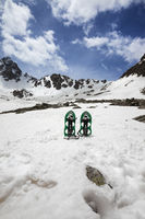 Pair of green snowshoes in snow. High snowy mountains and blue sky with clouds
