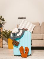 Summer vaction, suitcase with havaianas and hat.