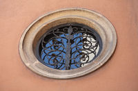 Antique round window with ornate metal bars on the plastered wall of old building. April 2013. Vienna, Austria