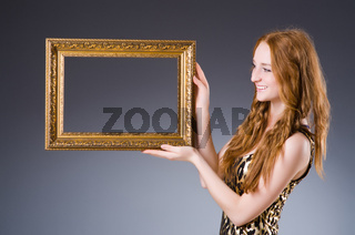 Redhead with picture frame against dark background