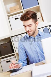 Junger Geschäftsmann rechnet mit Taschenrechner