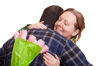 Man with bouquet of pink tulips hidden behind his back hugging elderly woman, isolated on white background. Mothers day, Valentines day, Easter and surprise Concept.