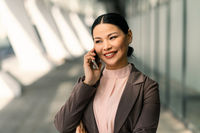 Smiling Asian businesswoman in suit talking on mobile phone against backdrop of business center. High quality photo