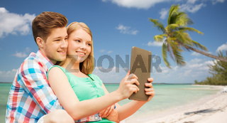 couple with tablet pc taking selfie over beach