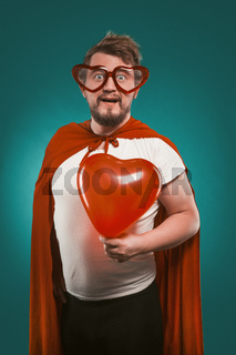 Superman In Love Holds Big Red Heart. Positive Man In Superhero Costume And Heart-Shaped Glasses Poses On Biscay Green Background. Valentine's day concept