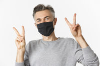 Concept of covid-19, social distancing and quarantine. Close-up of happy and cute middle-aged guy in black medical mask, showing peace signs and smiling, standing over white background