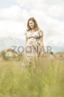 Beautiful pregnant woman in white summer dress in meadow full of yellow blooming flowers.