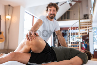 Sports physiotherapist massaging muscular strong man