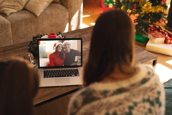 Rear view of woman and son having a videocall with couple in santa hats smiling on laptop at home