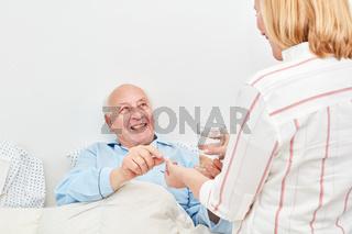 Pflegehilfe gibt Senior Medizin und Wasser