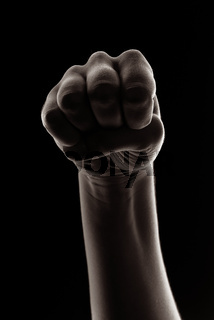 Woman hand in fist isolated on black background. Creative studio light.