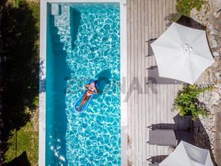 two person swim in the pool at the hotel. View from above, couple men and women in swimming pool of luxury vacation home in the Ardeche France