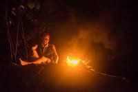 Guide auf dem Felsen beobachtet das Lagerfeuer im nächtlichen Dschungel von Ketambe