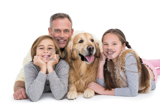 Portrait of happy family lying on the floor with their dog