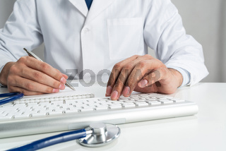 Doctor typing on wireless computer keyboard