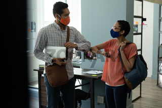Mixed race man and woman wearing masks bumping elbows in greeting