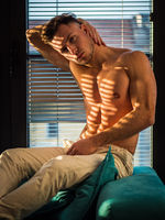 Pensive topless man in shadow stripes from window