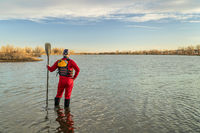 male stand up paddler dressed in a drysuit and life jacket