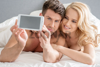 Middle Age Sweet Lovers Taking Photos on Bed