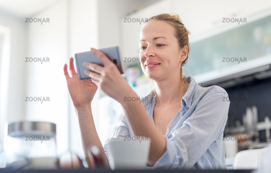 Young smiling cheerful pleased woman indoors at home kitchen using social media on mobile phone for chatting and stying connected with her loved ones. Stay at home, social distancing lifestyle.