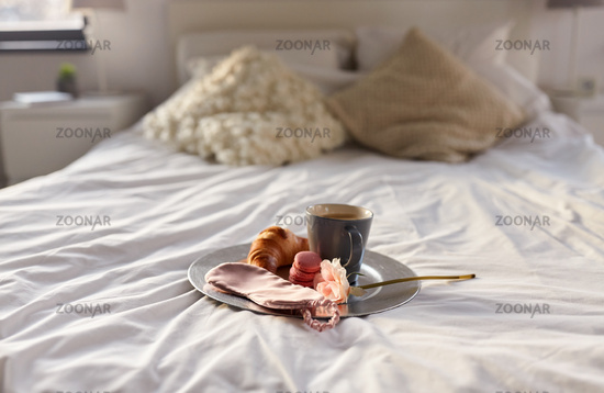 croissant, coffee and eye sleeping mask in bed