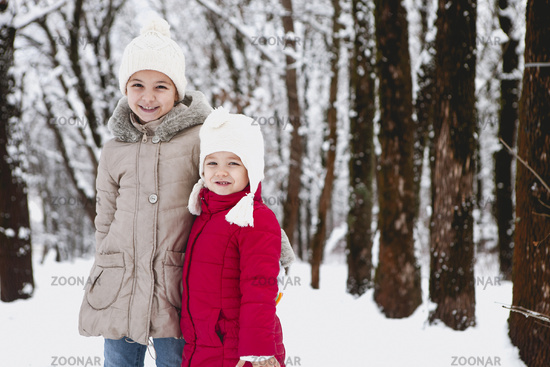 Little sisters in snowy forest